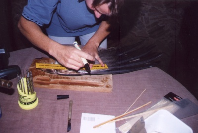 Gil measures the donor feathers prior to cutting them from the wing of a dead eagle
